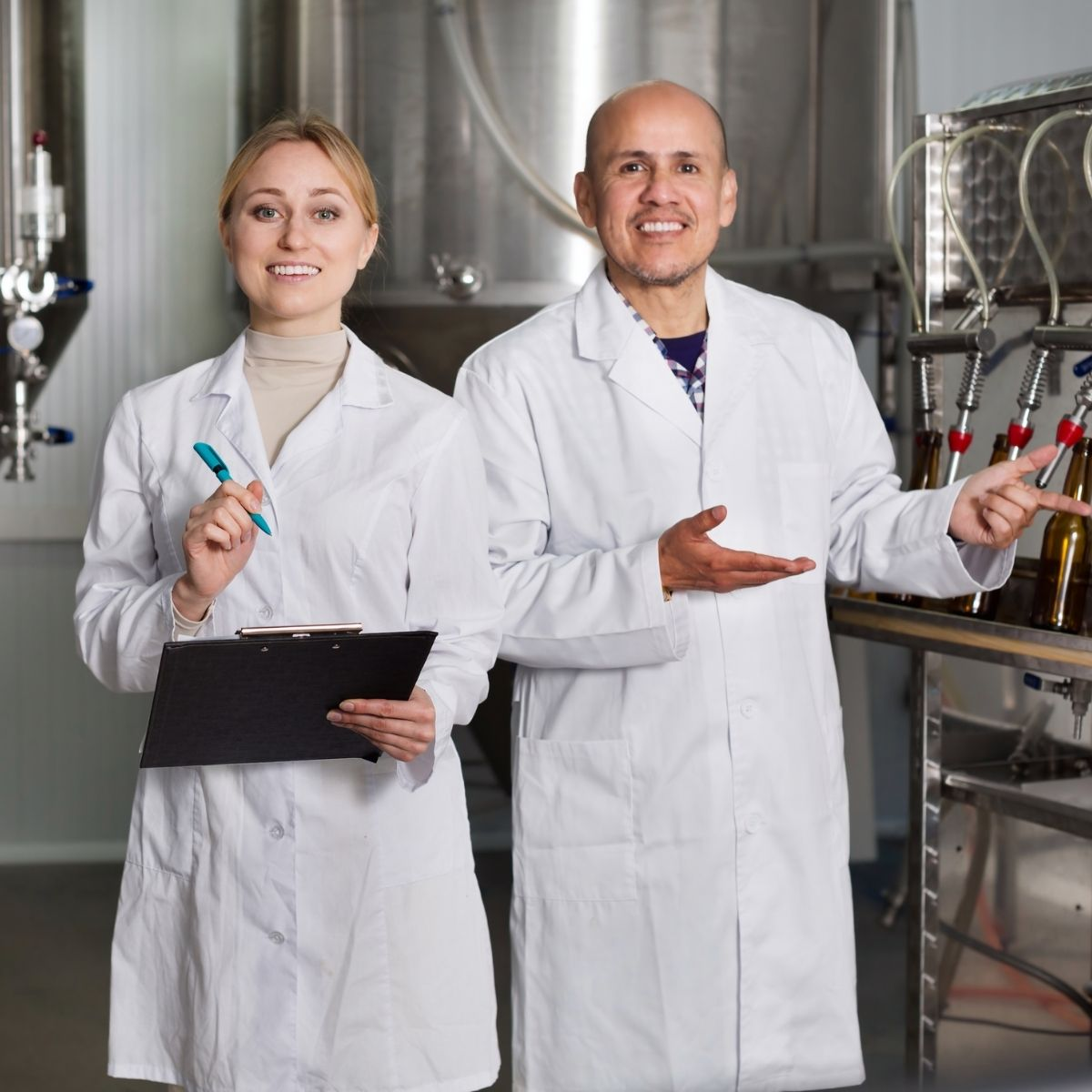 Two internal auditors standing in a food process area with clipboards, training in internal auditing.