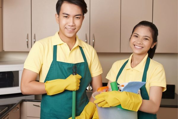 Man and woman cleaning and sanitising a food business