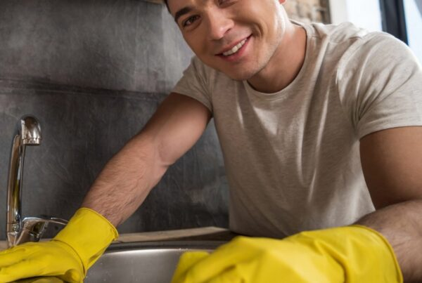 A food handler using a kitchen cleaning checklist to clean